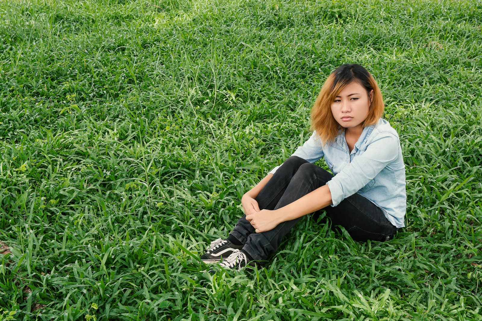 pensive woman sitting on the grass