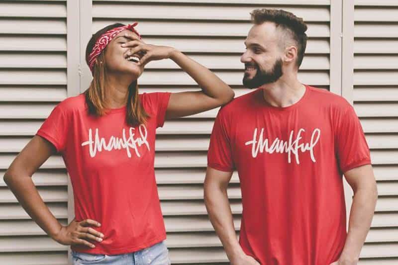 smiling man and woman wearing same shrit