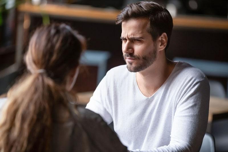 suspicious man listening to woman