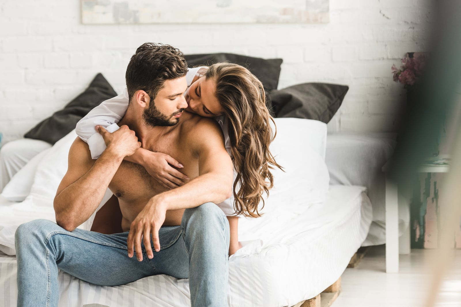 the brunette in bed hugs from the back of a handsome man