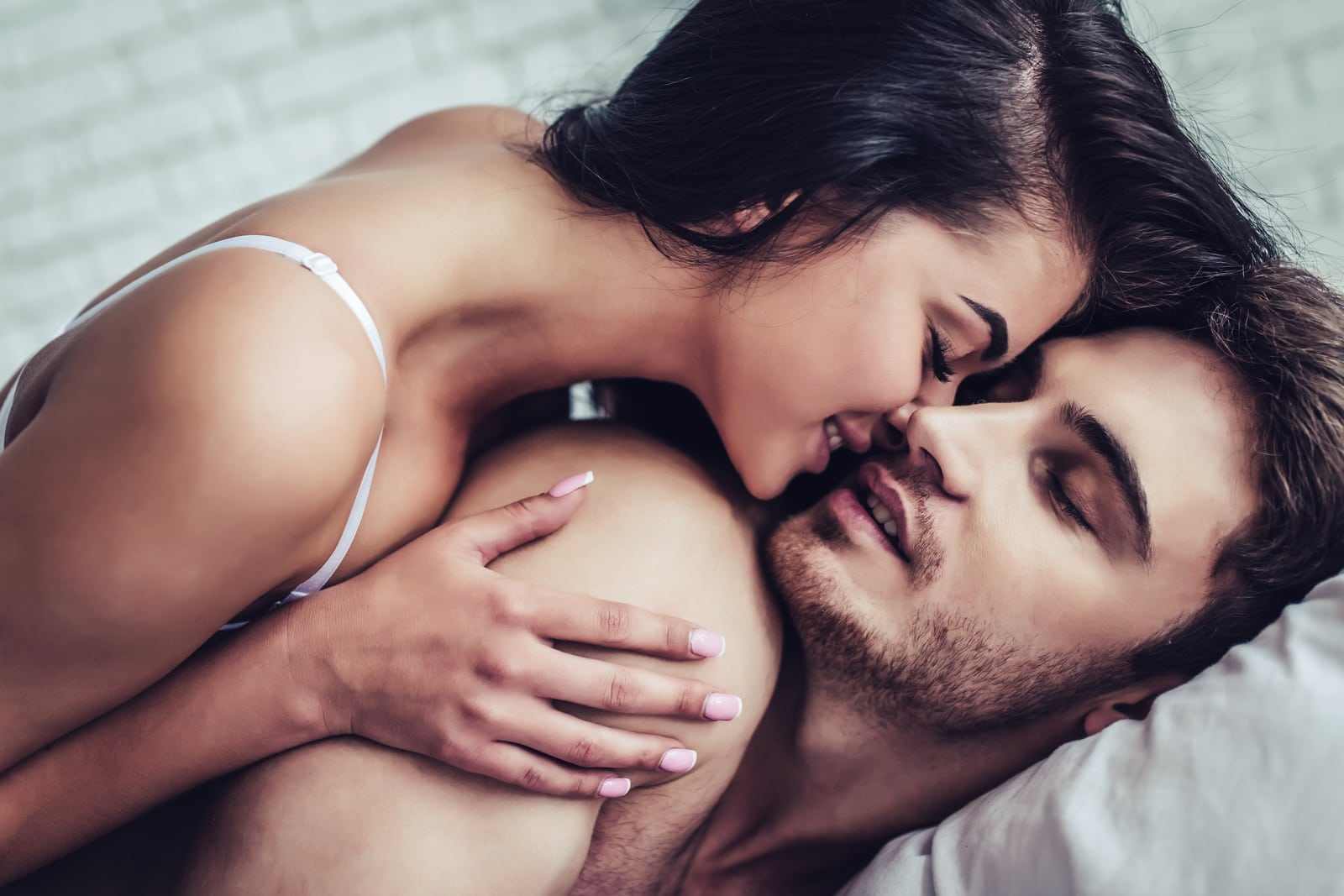 the brunette in bed lies on the man and passionately kisses him
