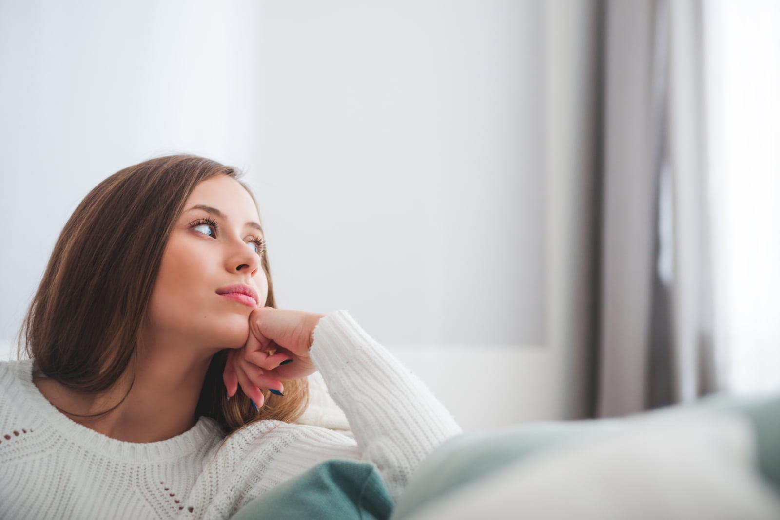 thoughtful woman at home looking at window