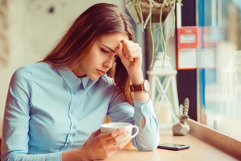 worried woman sitting and drinking coffee