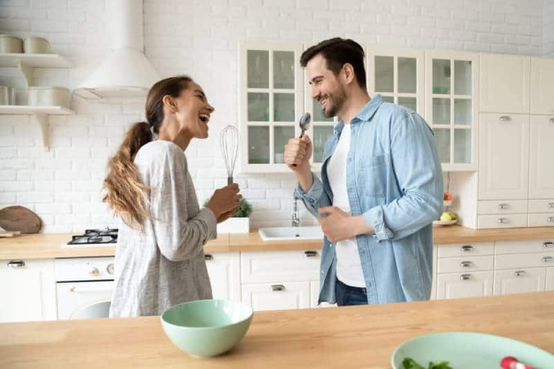 Funny young couple singing into kitchen ware microphones in the kitchen