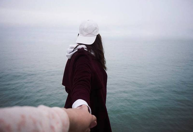man holds woman hands while she facing sea