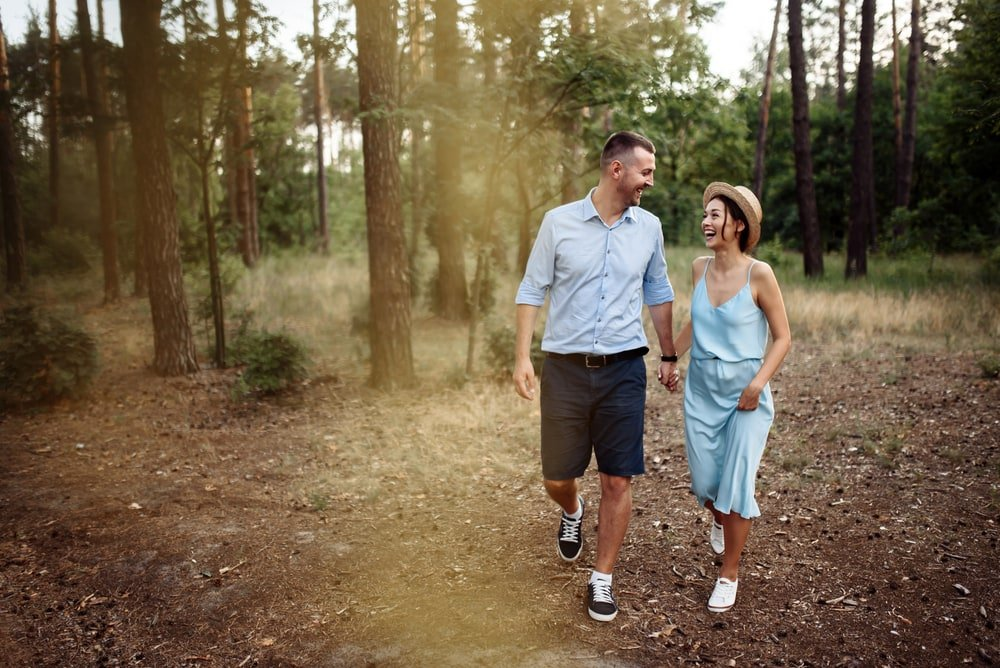 a smiling loving couple walking through the woods