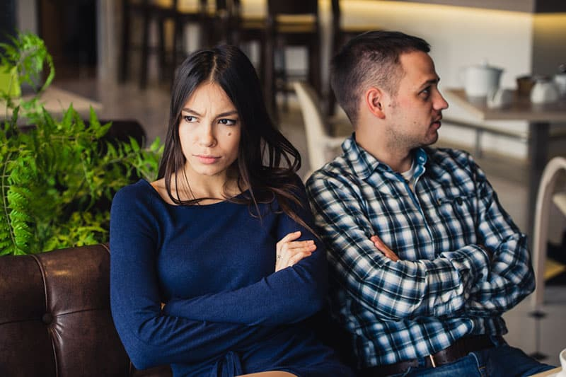 angry woman sitting next to her boyfriend