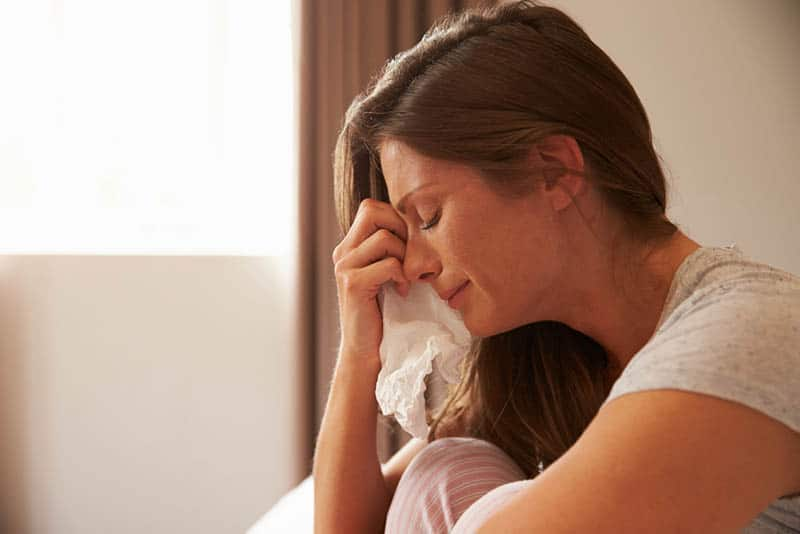 crying woman sitting at home