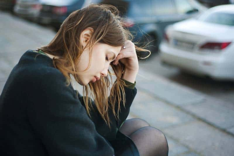 exhausted woman sitting on street outside