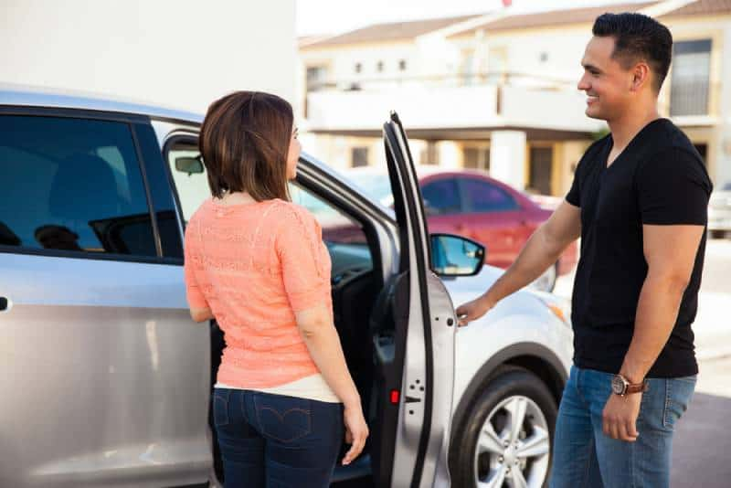 gentleman opening the car door for her girlfriend