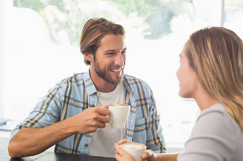 happy couple talks while drinking coffee