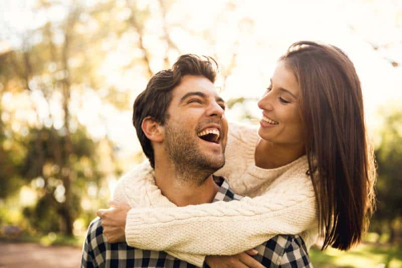 happy woman hugging smiling man from behind
