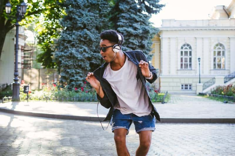 hipster man in white headphones and sunglasses dancing outdoor