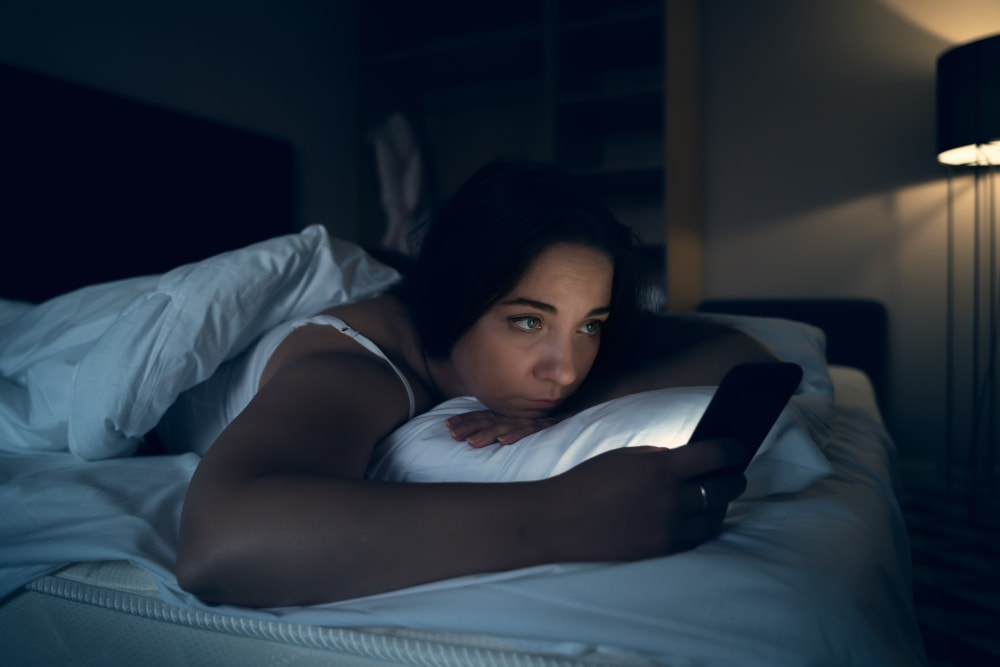 in the evening a sad brunette lies in bed and uses a cell phone