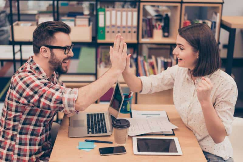 man and woman high five in office