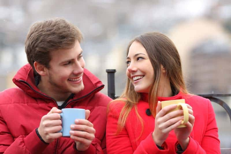 man and woman holding cup and smiling at each other