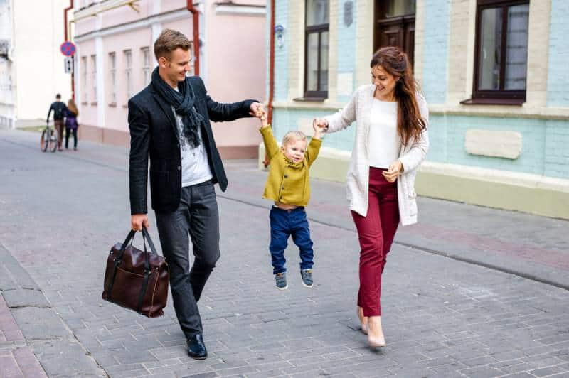 man and woman holding up kid on street