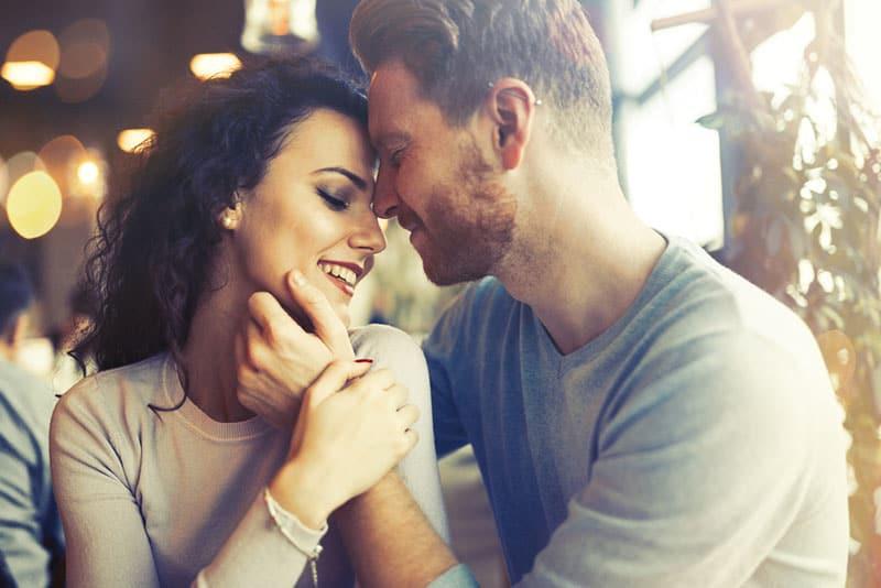 man cuddling womans face