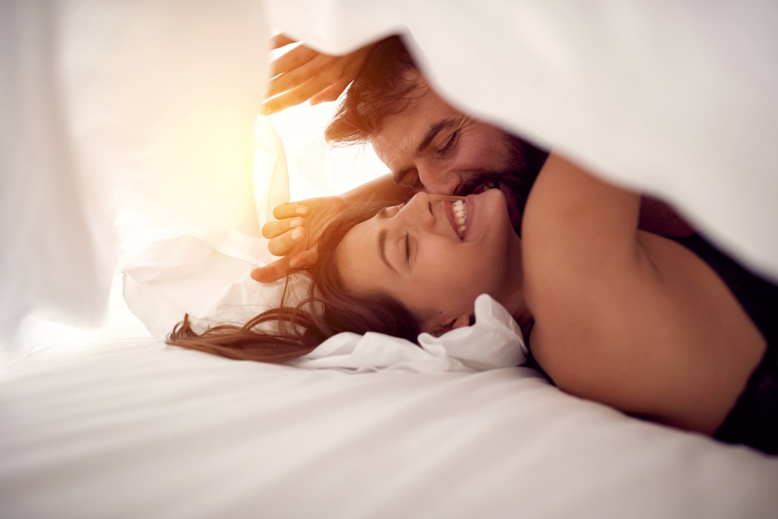 man kissing woman under the sheets