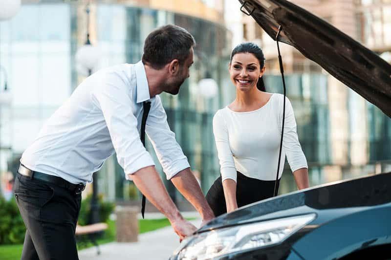 man trying to fix broken woman's car
