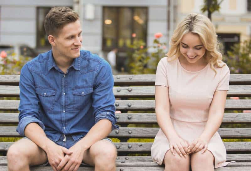 shy blonde girl sitting next to guy in blue shirt on a park bench