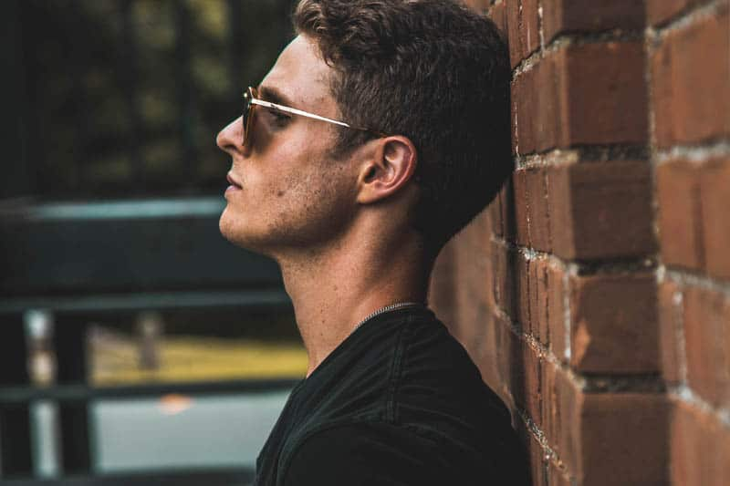 side view of man with sunglasses leaning on wall brick