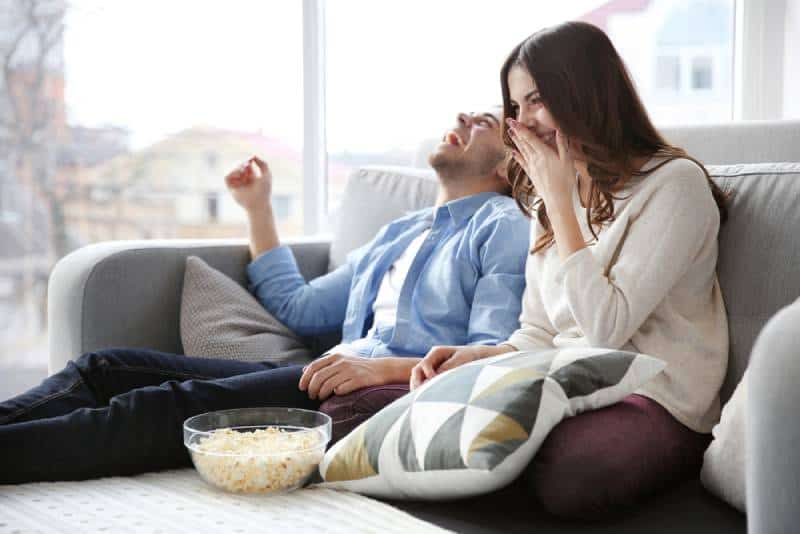 smiling couple watching TV on a sofa at home