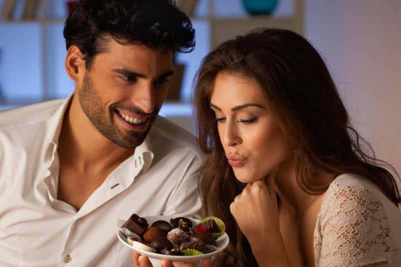 smiling man offering chocolate to woman