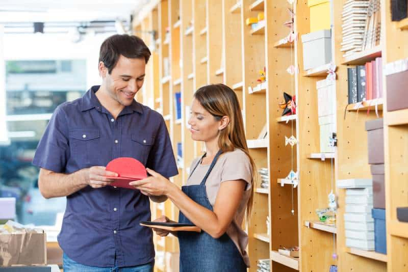 smiling man showing greeting cards to woman