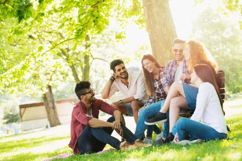 smiling young people sitting on grass beside tree