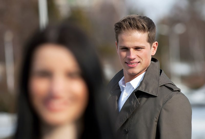 young man looking at woman passing by
