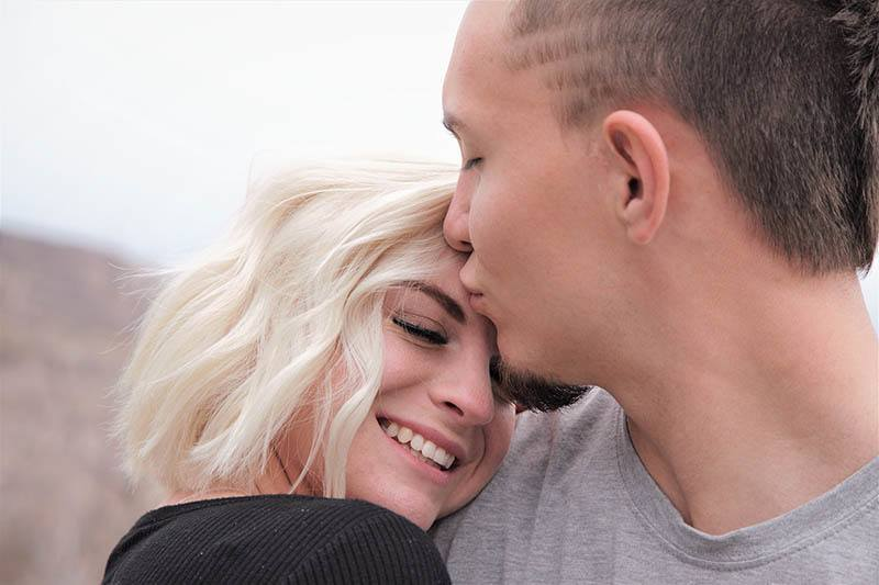 man kisses smiling woman forehead
