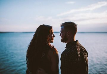 man and woman looking each other in front of sea
