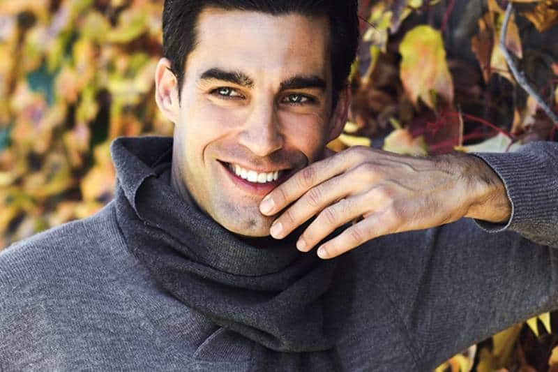 smiling man leaning on leaf wall