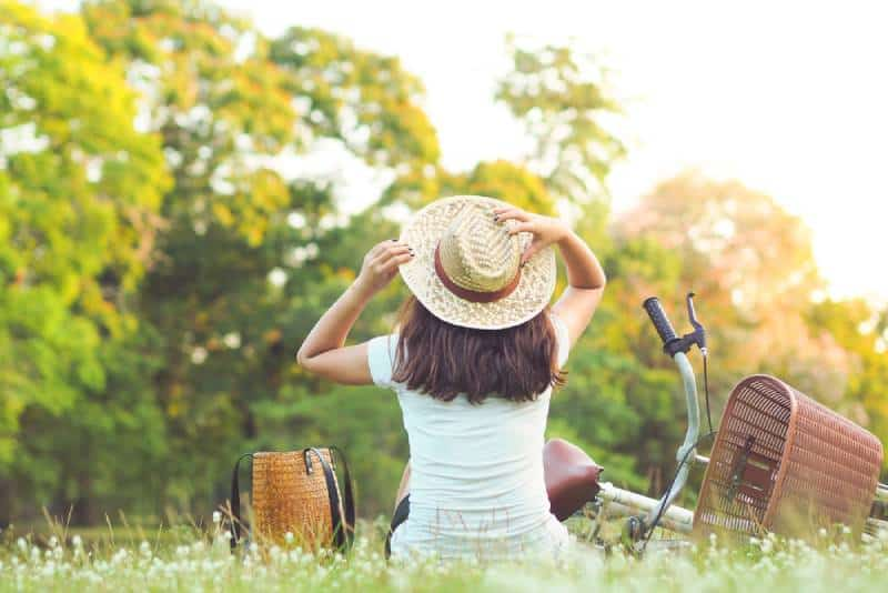 Woman is sitting near her bike in the park