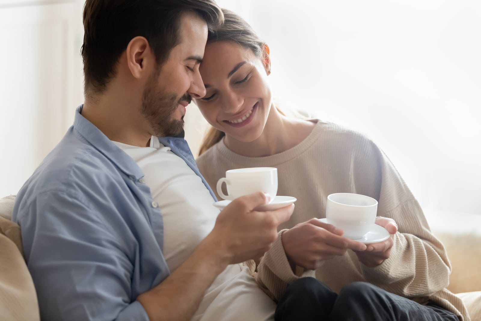 a happy couple in love sitting on a sofa and drinking coffee