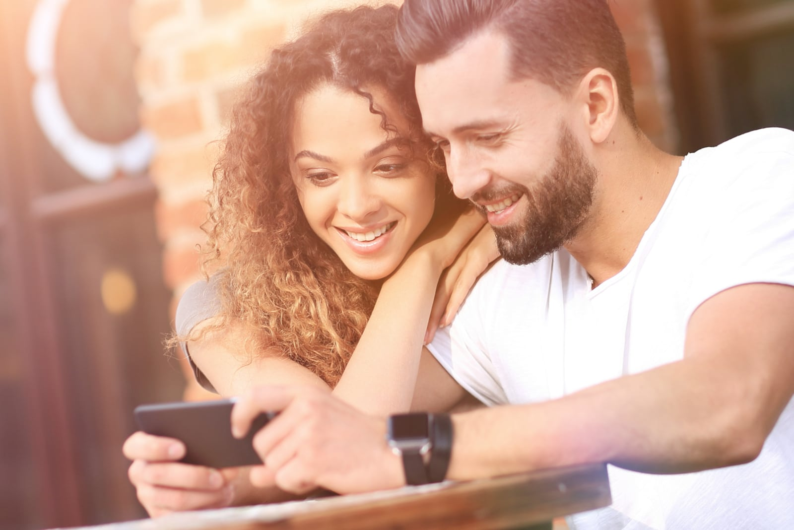a happy couple in love sitting on the terrace of a cafe and using a smartphone
