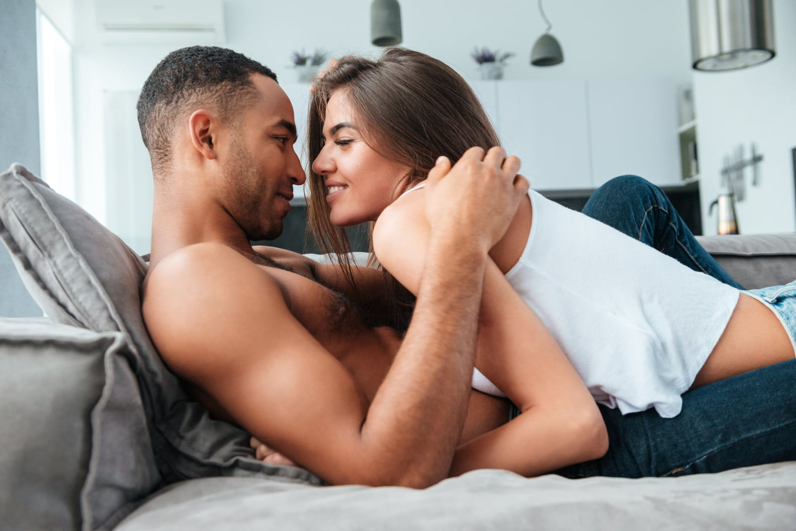 a happy loving couple caresses each other in bed