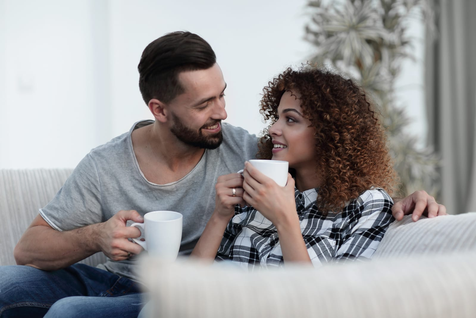 a loving couple drinking coffee on the sofa
