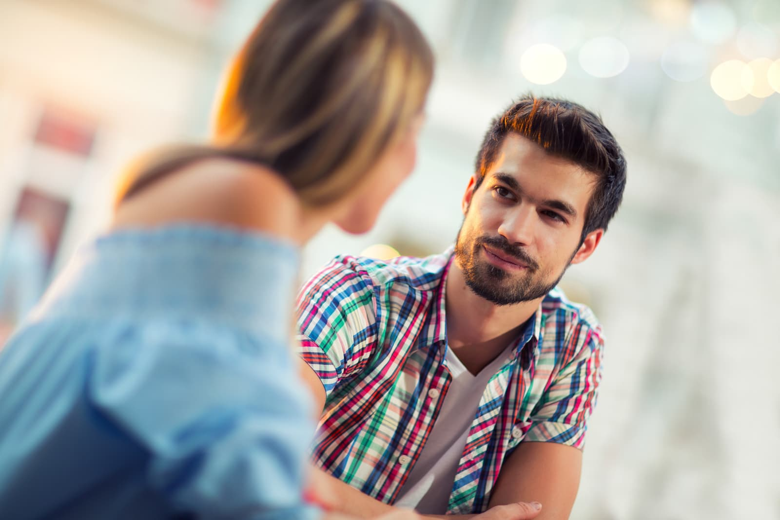 a man and a woman look at each other as they talk