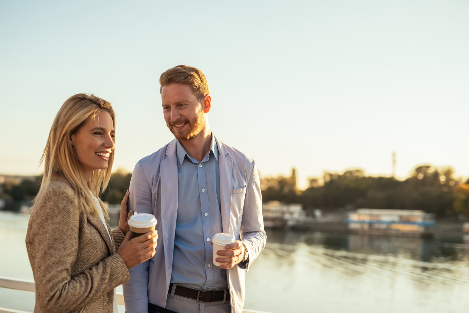 a man and a woman stand with coffee in their hands and talk