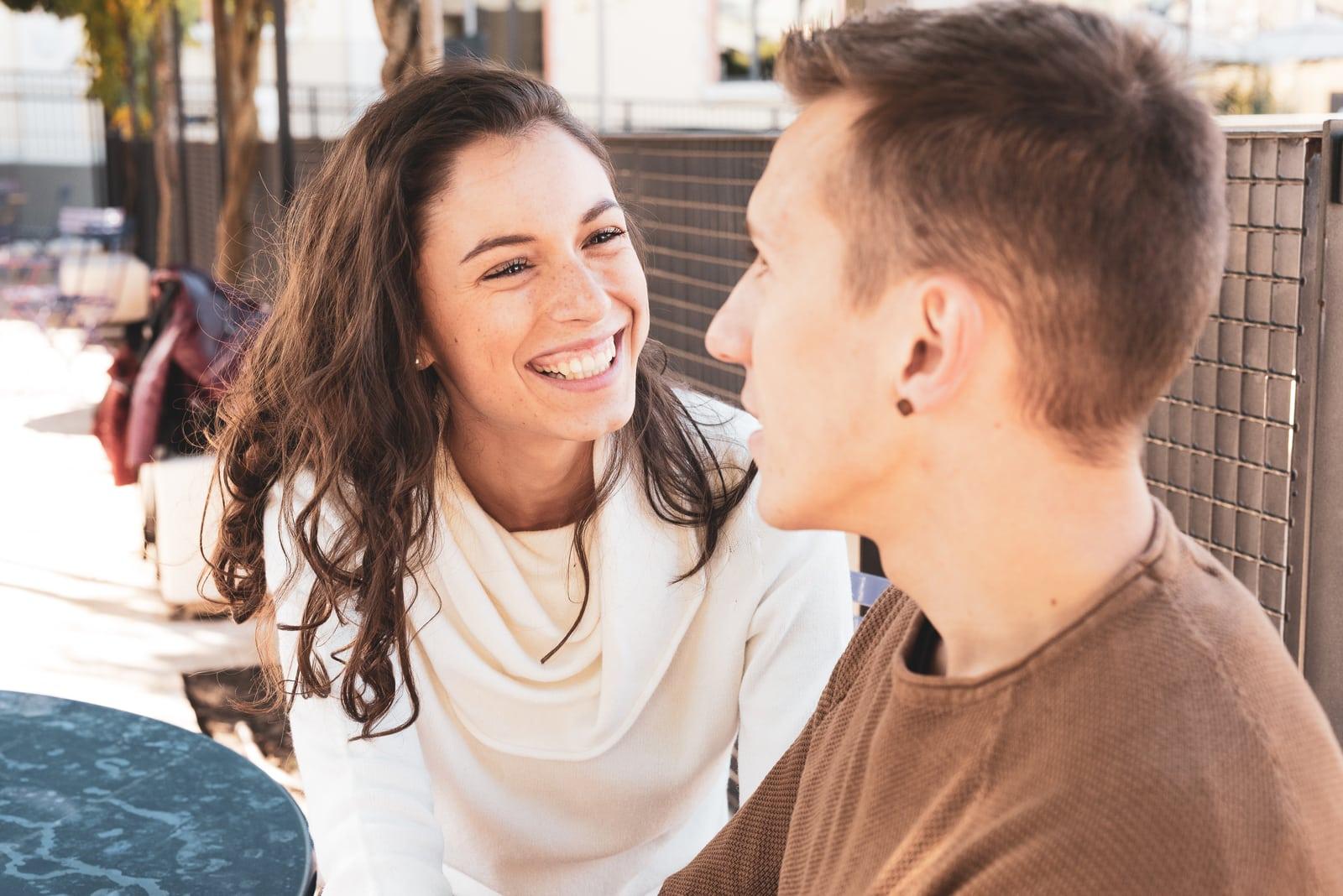 a smiling brunette and a man flirt
