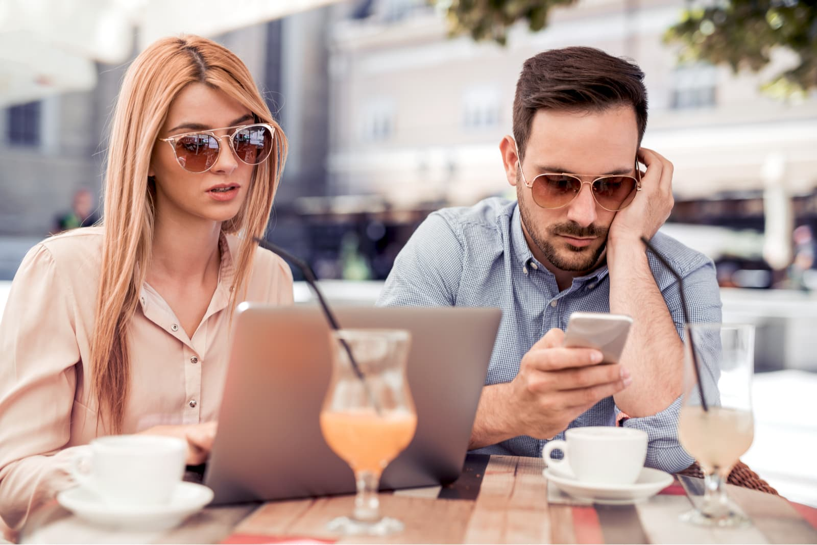 a woman and a man are sitting while he is typing on the phone