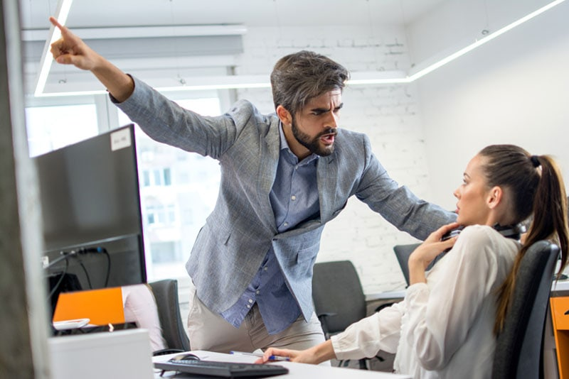 angry man yelling on work colleague