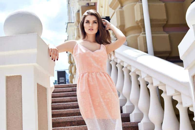 beautiful woman wearing dress and standing on stairs
