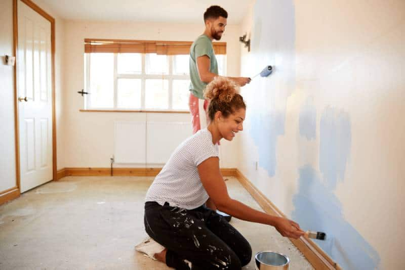 couple decorating room, painting wall in blue