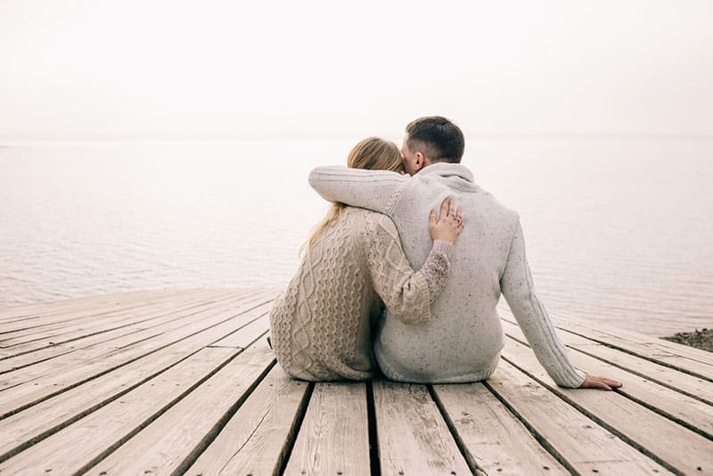 couple in hug sitting by the sea