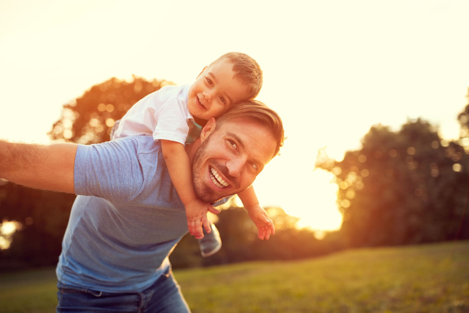father and son having fun at sunset in nature
