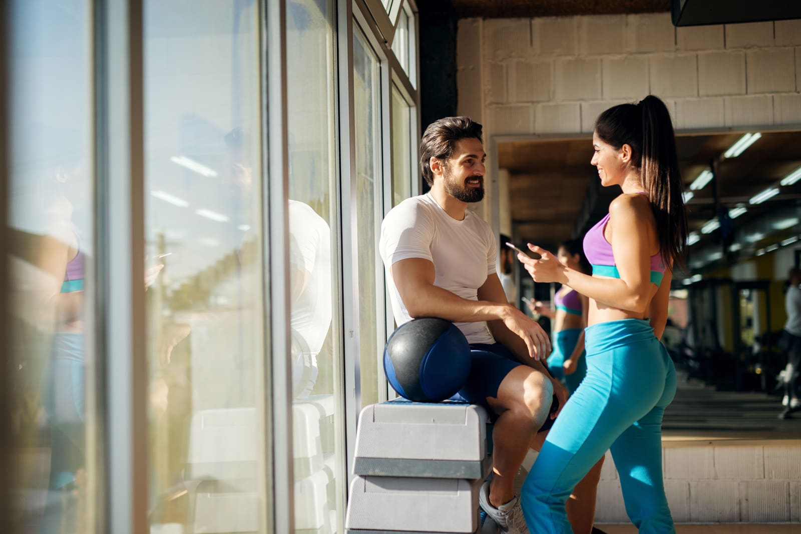 in the gym, a beautiful woman and a handsome young man are flirting