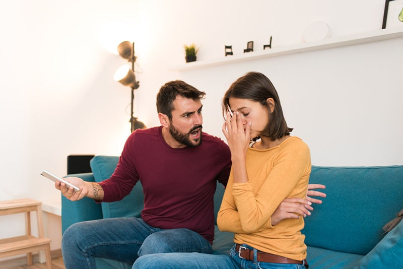 man arguing with girlfriend in the living room